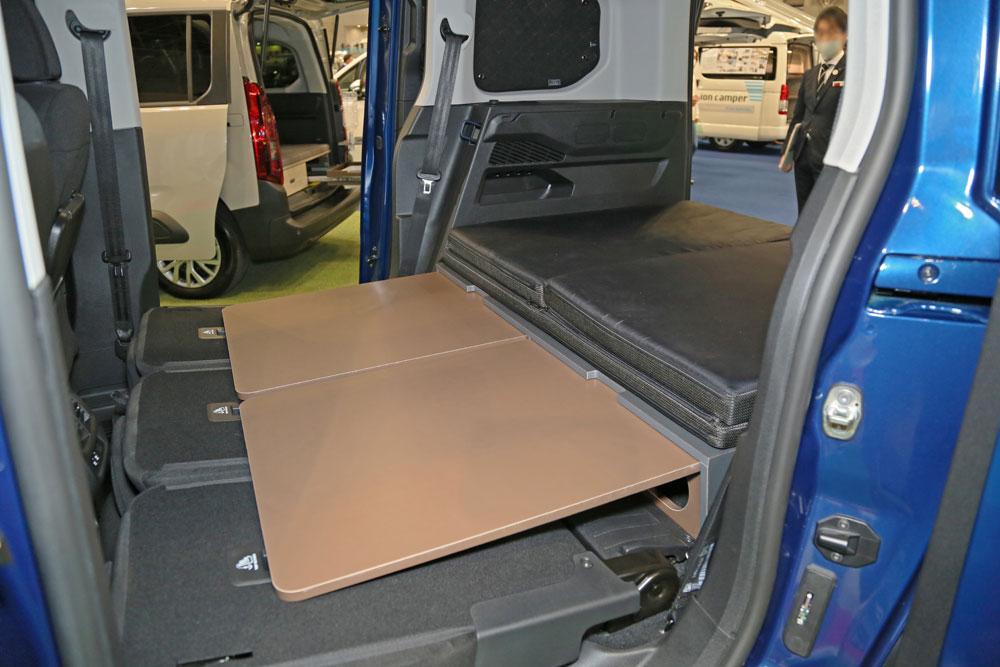 2列目シートのシートバックを倒し、荷室との段差を埋めるボードを引き出した状態。フラットベッドを敷いた様子も撮影することができた。(ジャパンキャンピングカーショー2021)
