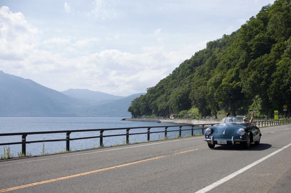 観光名所である支笏湖の湖畔ゆくポルシェ356Bロードスター。